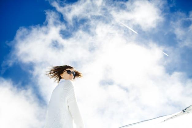 雪と太陽で休んで幸せな女の子 無料写真