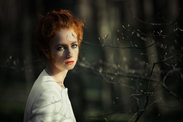 Задуманная рыжеволосая девушка с красными губами смотрит в кадр Бесплатные Фотографии