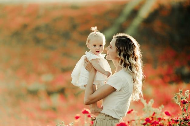 ケシ畑で赤ちゃんに笑顔の女性 無料写真