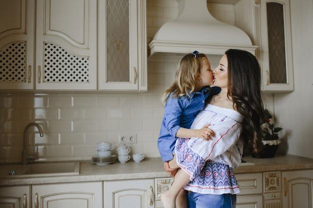 ママは台所で小さな娘にキスします。 無料写真