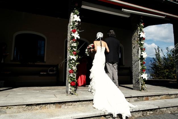 Невеста в длинном платье входит в старую часовню Бесплатные Фотографии