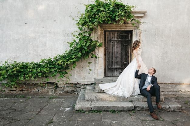 古い家の近くで美しい花嫁が撮影されています 無料写真