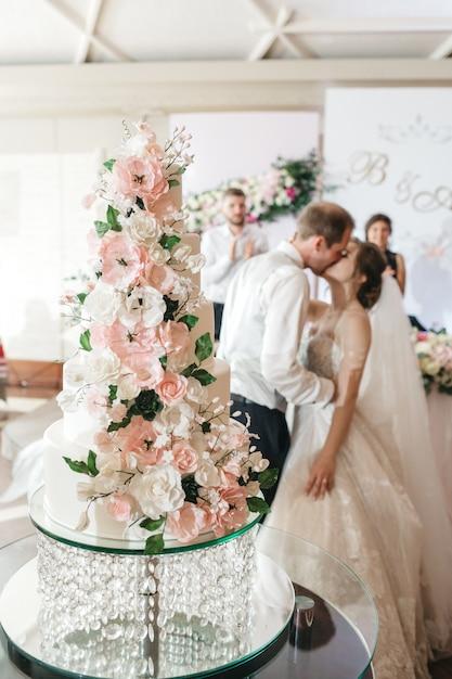 Счастливые невесты целуют торт в день своей свадьбы Бесплатные Фотографии