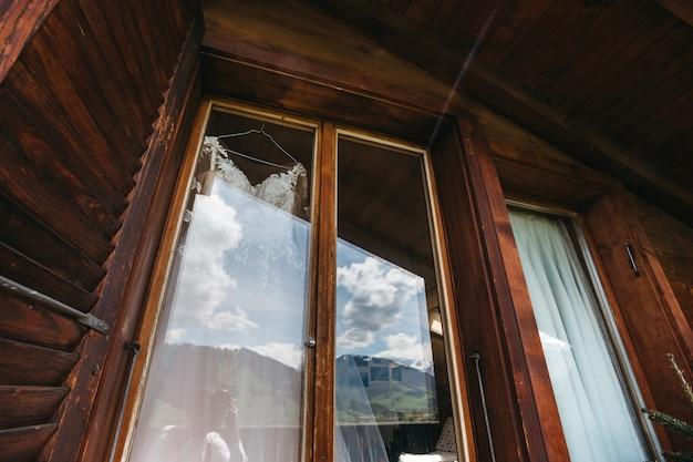 Свадебное платье вешает на окно в огромном деревянном гостиничном номере Бесплатные Фотографии