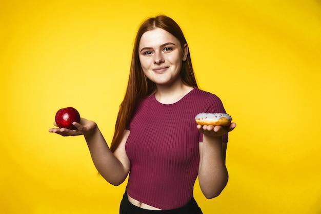Улыбающаяся рыжая кавказская девушка держит яблоко в одной руке и пончик в другой руке Бесплатные Фотографии
