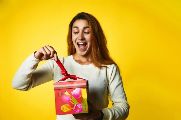 Возбужденная рыжая кавказская девушка открывает подарок с удивленным лицом Бесплатные Фотографии