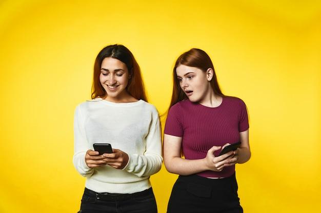 Две улыбающиеся кавказские девушки с современными смартфонами смотрят на экран телефона Бесплатные Фотографии