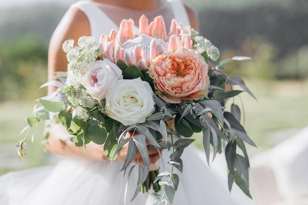 花嫁はバラ、ユーカリ、巨大なプロテアで美しいブライダルブーケを保持しています 無料写真