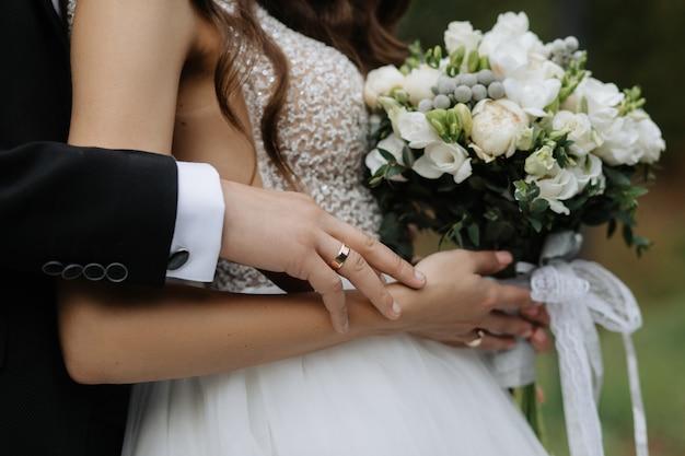 花嫁は美しい花束を持っており、新郎は背中を抱擁します 無料写真