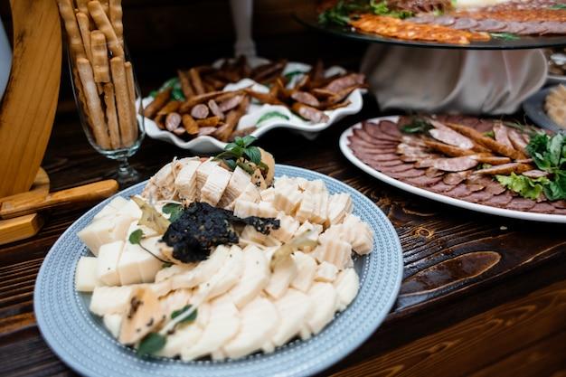 木製テーブルの上のチーズセット、ソーセージセット、塩味のスナック 無料写真
