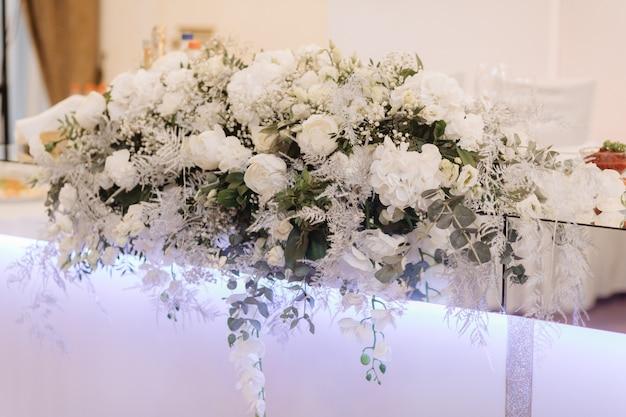 テーブルの上に白いバラとユーカリの大きな花束が立つ 無料写真