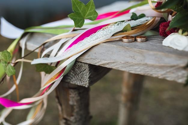 Обручальные кольца лежат на деревянном столе возле букета с множеством лент Бесплатные Фотографии