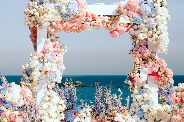 Красиво украшенная свадебная арка у моря Бесплатные Фотографии
