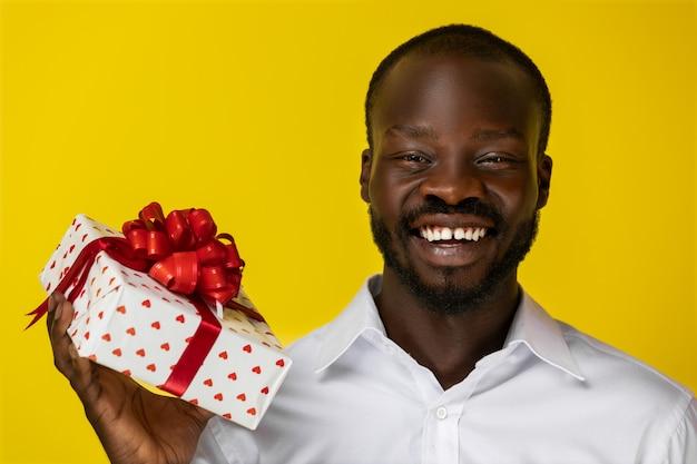 Красивый негр улыбаются в камеру и держит подарочную коробку Бесплатные Фотографии