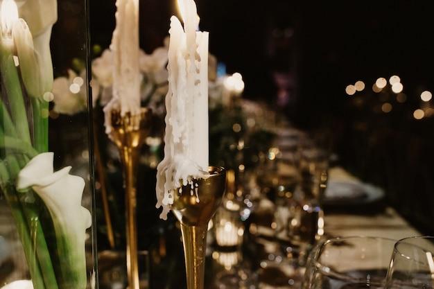 結婚式のテーブルの上の黄金の燭台のろうそく 無料写真