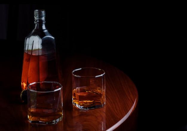 Бутылка и бокалы ликера на деревянный стол Premium Фотографии
