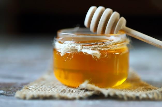 蜂蜜の瓶と蜂蜜のひしゃく。 Premium写真