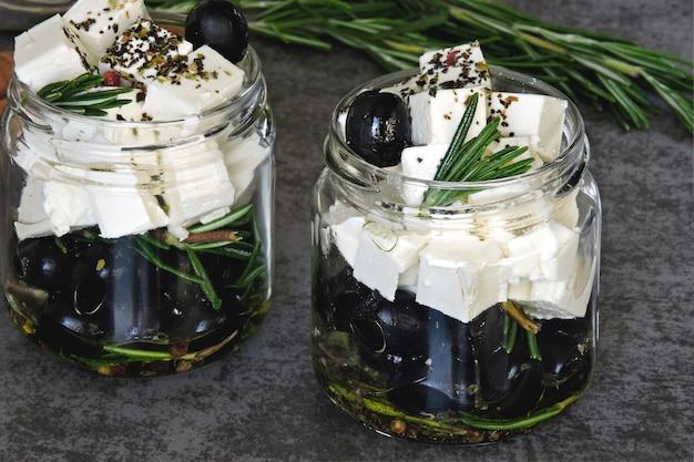 Кусочки сыра фета и оливки в баночках с розмарином и специями. кето закуска Premium Фотографии