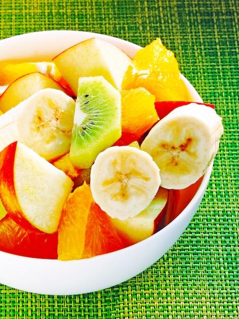 Чаша фруктовый салат. фруктовый салат с киви, бананом, апельсином и яблоком. концепция фитнес-питания. Premium Фотографии