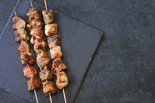 Аппетитные румяные шашлыки на темной каменной поверхности. вид сверху. Premium Фотографии