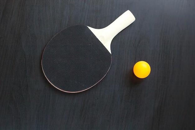 卓球や卓球ラケットとボール、黒い背景に Premium写真