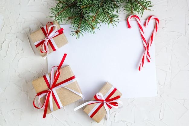 キャンデー杖、クリスマスツリーの枝、ギフトを置く白紙 Premium写真