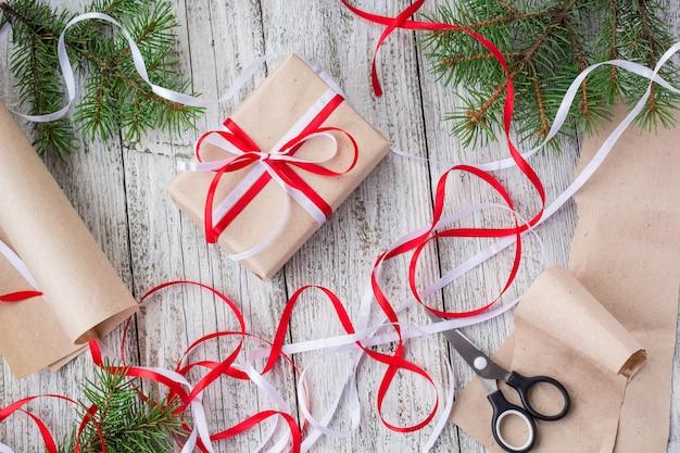 Упаковка рождественских подарков в крафт-бумагу с красными и белыми лентами Premium Фотографии