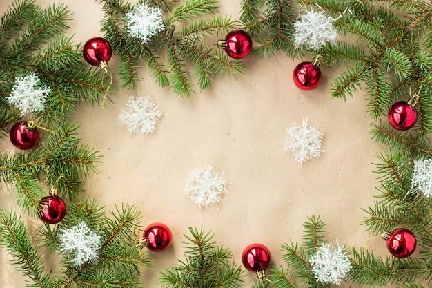 Праздничная рождественская граница с красными шариками на еловых ветках и снежинками на деревенском бежевом фоне Premium Фотографии