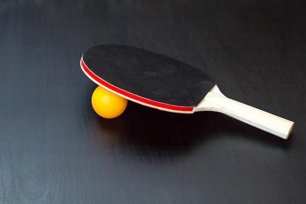 卓球または卓球ラケットと黒いテーブルの上のボール Premium写真