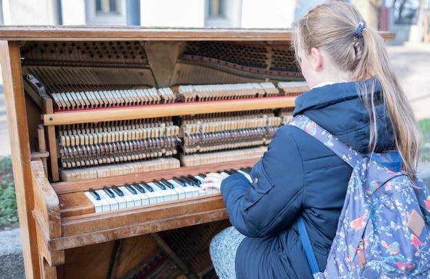 路上で女の子が古いピアノを弾きます。 Premium写真