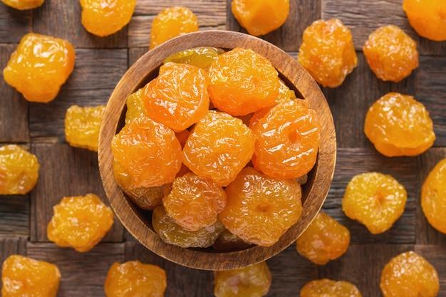 砂糖漬けのフルーツ、木製のボウル、トップビューでパラダイスアップル。 Premium写真