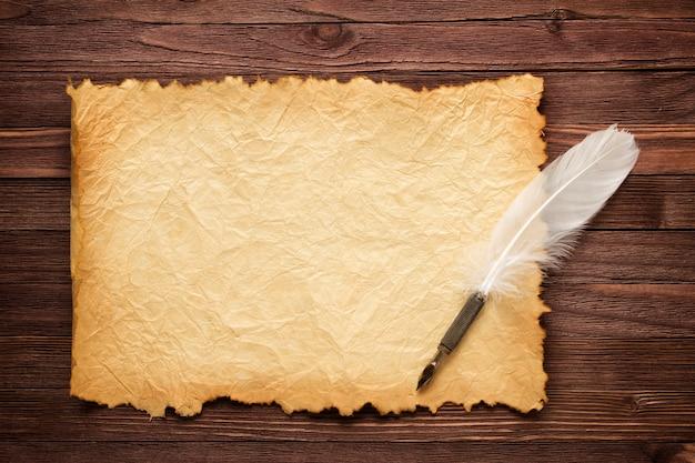 Белое перо и старая бумага на деревянной поверхности | Премиум Фото