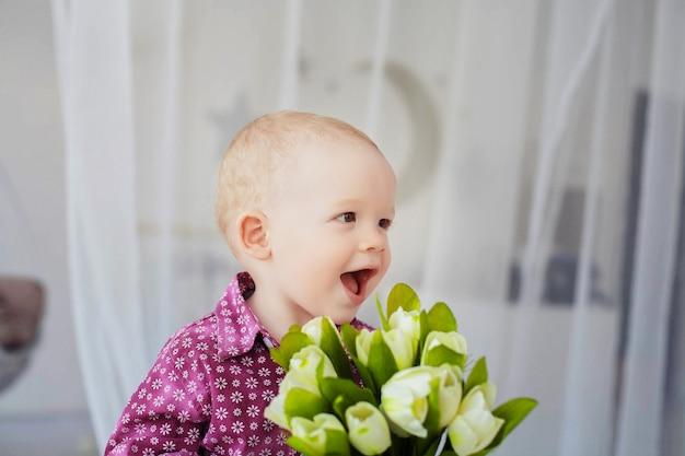 花の花束を持つ小さな子供。 Premium写真