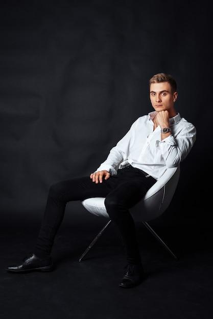 Мальчик в белой рубашке сидит в кресле. концепция жизни Premium Фотографии