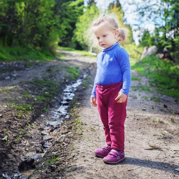 小さな子供は森の中の小川を見ます。 Premium写真