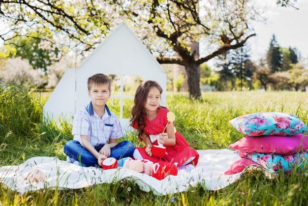 スタイリッシュな小さな男の子とピクニックに美しい巻き毛の女の子。幼年期および生活様式の概念。 Premium写真