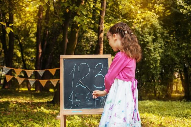女子高生は、黒板の近くに数字を教えています。学校に戻る。教育、学校のコンセプト Premium写真