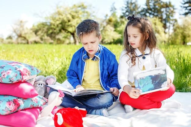 Двое детей читают книги в парке. концепция образования Premium Фотографии