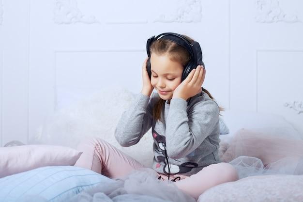 ベッドの上に座って、オーディオブックを聞いて子供女子高生。子供の頃、教育、音楽。 Premium写真