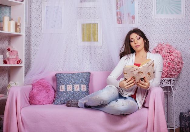 ピンクの部屋で面白い本を読んで美しい少女。 Premium写真