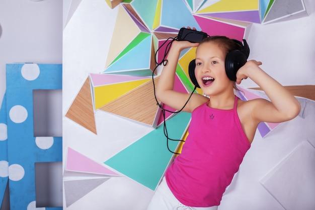 Жизнерадостная девочка с наушниками слушает музыку и поет Premium Фотографии