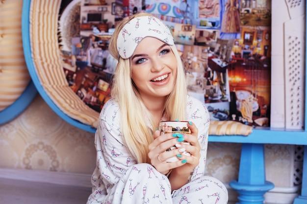 Улыбающаяся блондинка сидит на полу в пижаме и пьет кофе. маска для сна. концепция образа жизни, отдыха, завтрака, сна. Premium Фотографии
