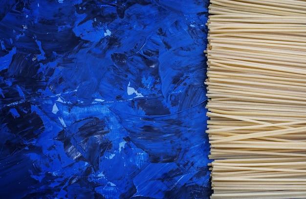 Синий фон с спагетти. Premium Фотографии