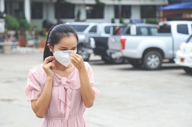 Защитная маска азиатской девушки нося с чувством холода лихорадки для концепции вируса короны Premium Фотографии