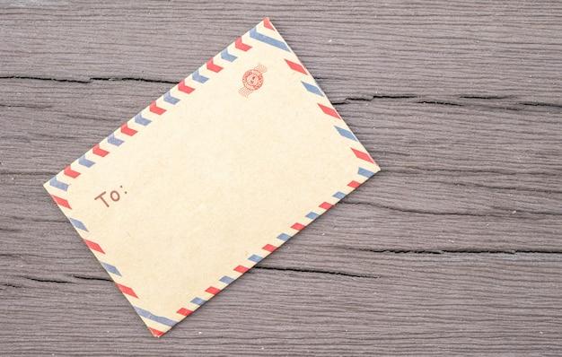 織り目加工の古い木製のテーブルの上の茶色のクローズアップ封筒 Premium写真