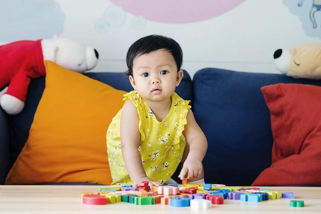 クローズアップ少女は、リビングルームのバックグラウンドでソファの上の木製のジグソーパズルのおもちゃを遊ぶ Premium写真
