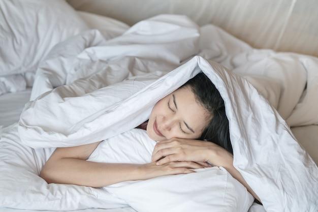 クローズアップアジアの女性が寝室で毛布の下のベッドで寝る Premium写真
