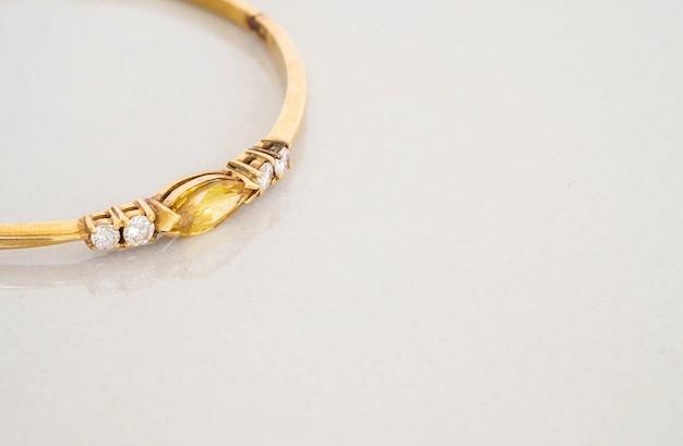 Крупным планом золотой браслет с желтой галькой на сером мраморном камне Premium Фотографии