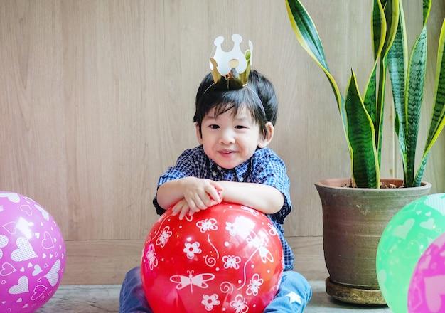 コピースペースと織り目加工の背景の部屋で誕生日パーティーで紙の王冠とバルーンのクローズアップかわいいアジア子供 Premium写真
