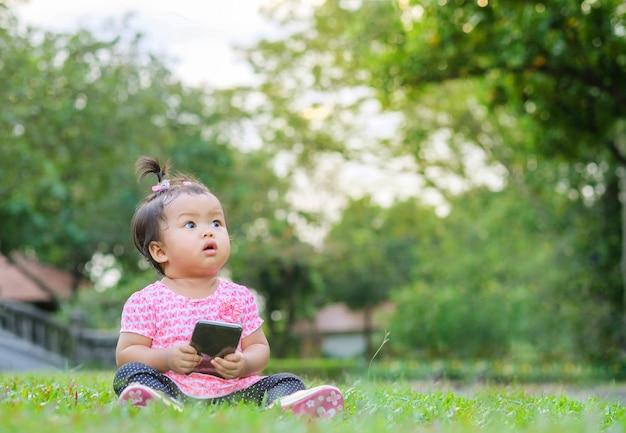 クローズアップの小さな女の子が芝生の床の上に座るし、パークビューの背景に画像のスペースを見てください。 Premium写真